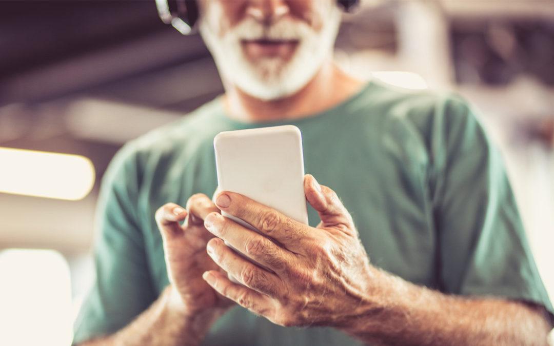 Foto homem idoso usando o celular na academia