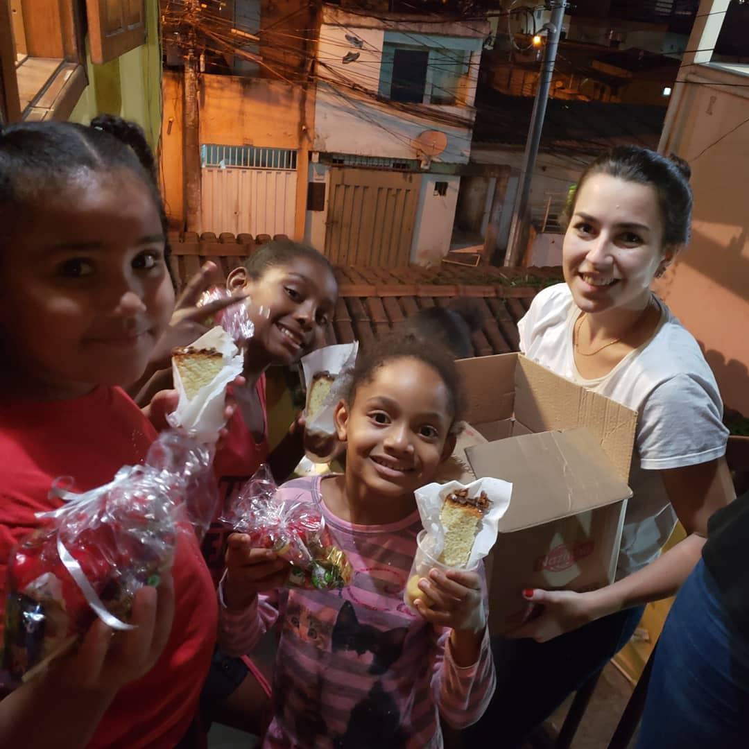 foto de uma integrante da equipe da agência de publicidade bh 2 Pontos comunicacão com crianças sendo presenteadas com kits de doces e bolos