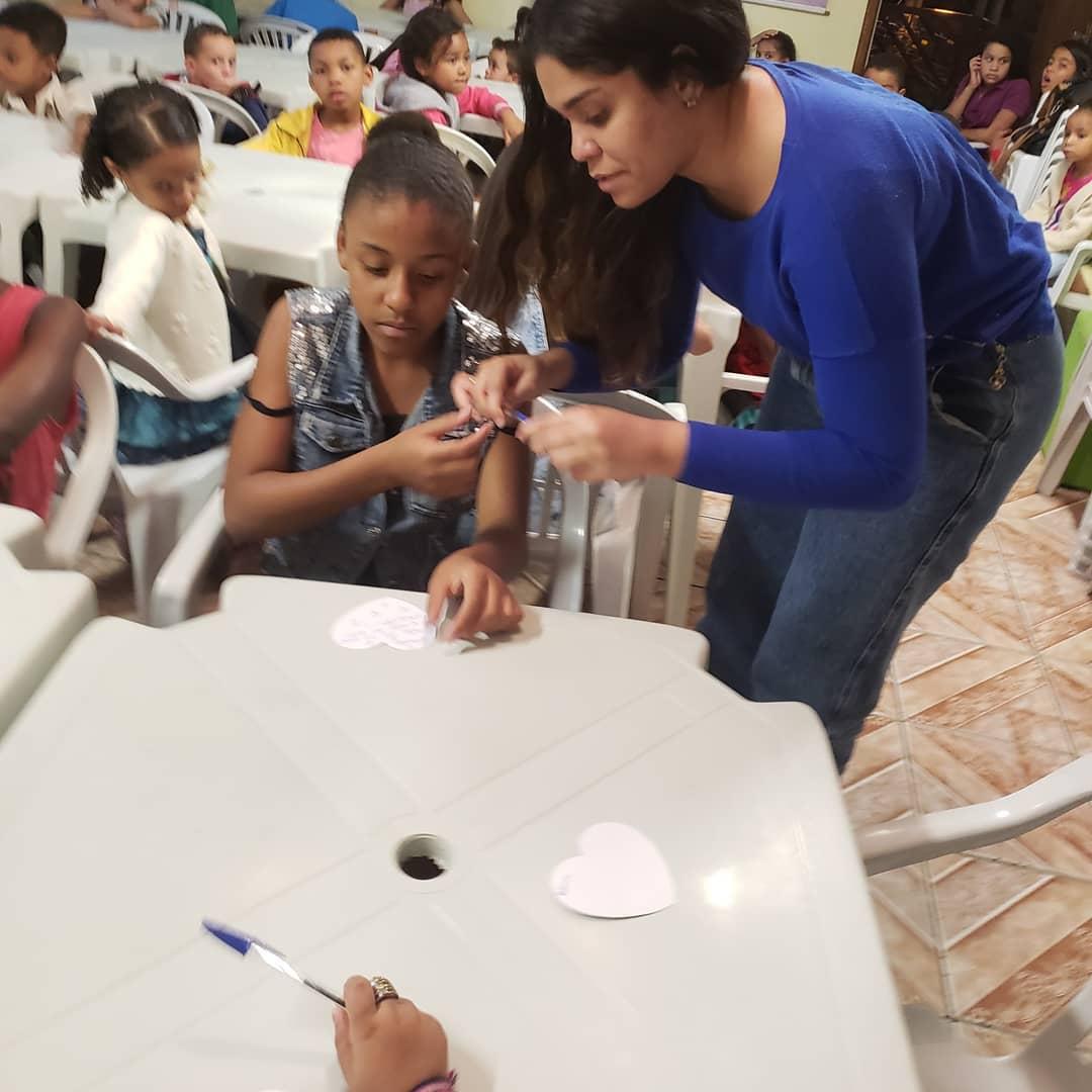 Foto de mulher ajudando as crianças a escreveram cartões de presente para as mães