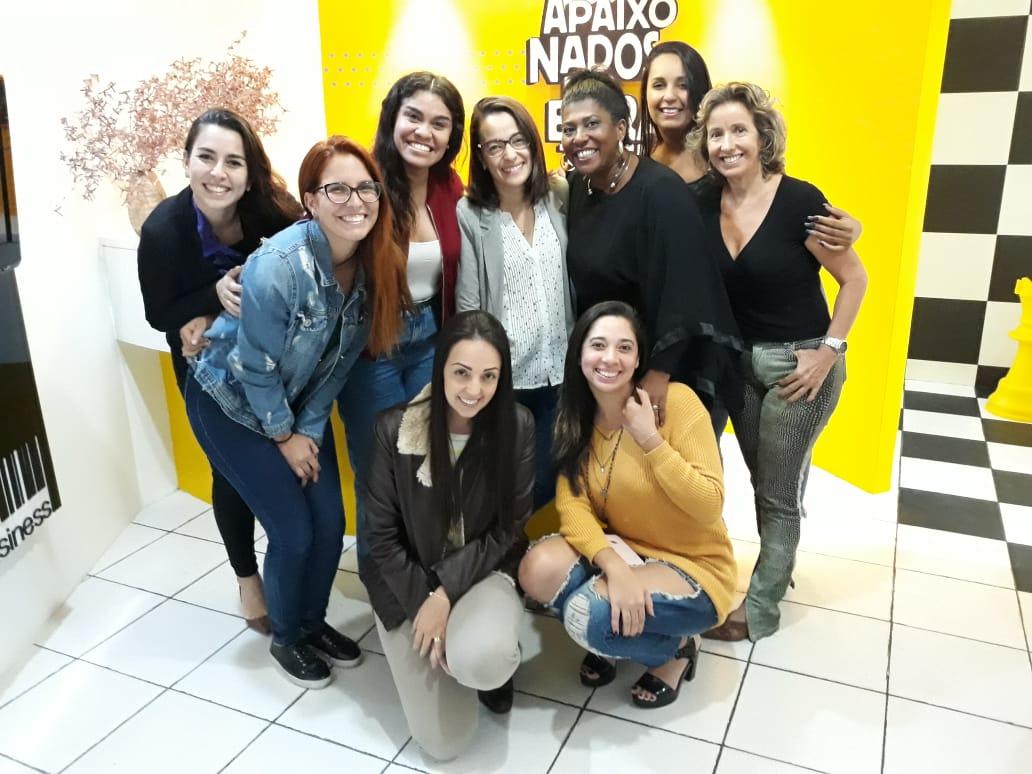 Foto das mulheres da equipe da agência de publicidade bh 2 Pontos Comunicação posando em frente a recepção da agência de marketing bh com as parceiras do projeto Pontos solidários. Branding