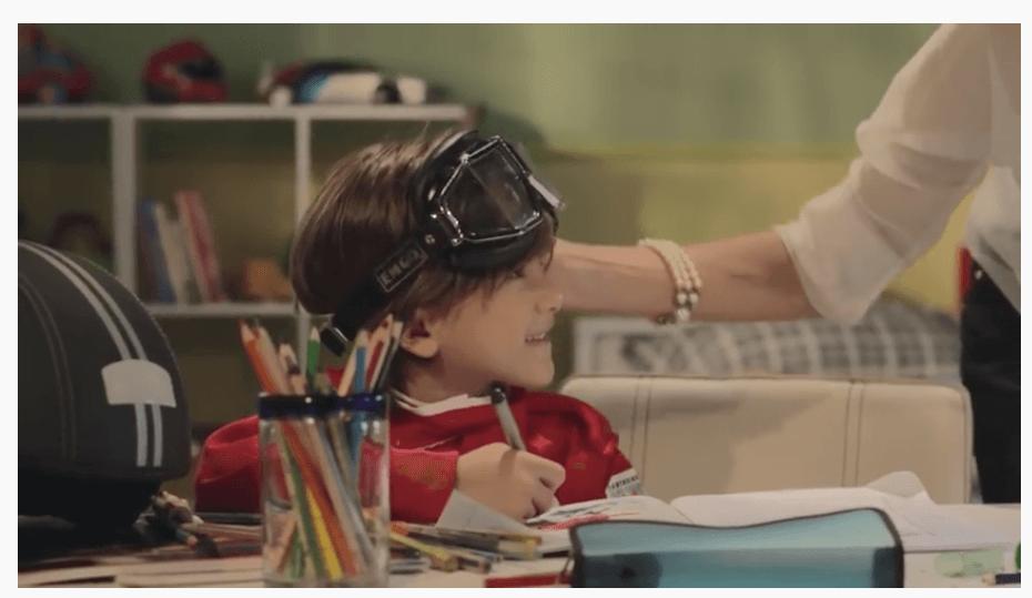 Criança com óculos olhando para mãe enquanto desenha. Publicidade